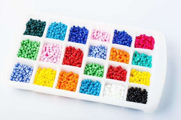 Różnokolorowe koraliki na białym plastikowym pudełku z bliska