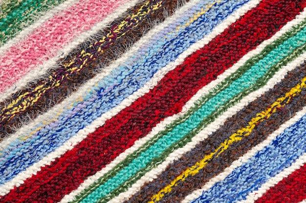 Różnokolorowe paski na powierzchni dzianiny. tło zbliżenie tekstylne dywany retro lub dywany. tekstura tkaniny jest połączeniem z geometrią linii. produkt ręcznie robiony