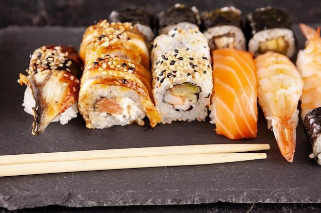 Różnorodna mieszanka rolek sushi na czarnym tle na zdjęciu studyjnym