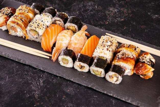 Różnorodna mieszanka różnych rodzajów sushi na ciemnym kamiennym tle