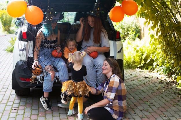 Różnorodna rodzina świętuje halloween w bagażniku samochodu. dziewczyny zabawy na świeżym powietrzu w jesienny dzień. wysokiej jakości zdjęcie. zostań w domu na halloween. świętowanie w odosobnieniu. cukierek albo psikus.