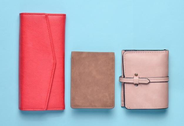 Różnorodne damskie skórzane portfele na niebieskim pastelowym tle, akcesoria damskie, widok z góry, minimalizm