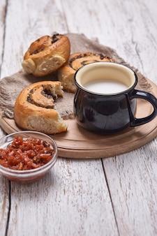 Różnorodne domowe bułeczki z ciasta francuskiego cynamon podawane z kubkiem mleka, dżemem, masłem jako śniadanie na drewnianym stole z białej deski