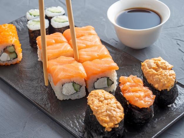 Różnorodne japońskie bułki i sushi na czarnym talerzu z teksturą. widok z boku. pałeczki bambusowe trzymające pojedynczą rolkę