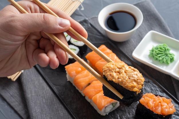 Różnorodne japońskie bułki i sushi na teksturowanej czarnej płycie. widok z boku. bambusowe kije mieszczą jeden gunkan. ścieśniać
