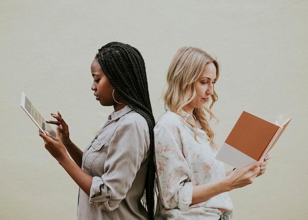 Różnorodne kobiety czytające książkę i korzystające z tabletu