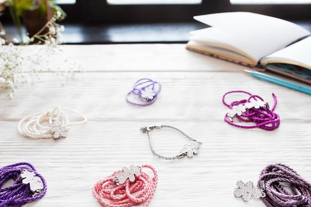Różnorodne kolorowe bransoletki kobiece na białym tle. ręcznie robione akcesoria dla kobiet na drewnianym stole, modnej kobiety lub dziewczyny w miejscu pracy