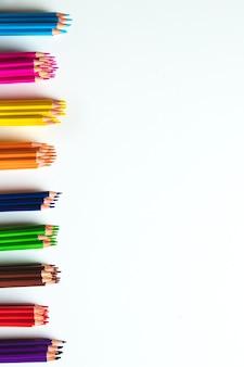 Różnorodne kolorowe kredki na białym tle