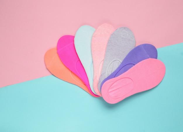 Różnorodne kolorowe skarpetki na kolorowej pastelowej powierzchni. minimalizm, widok z góry