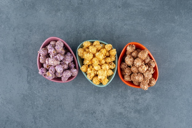 Różnorodne kolory cukierków popcornowych w małych miseczkach z marmuru