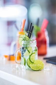Różnorodne lemoniady w słojach z masonem z pomarańczową limonką, cytryną, truskawkami tange i świeżymi owocami.