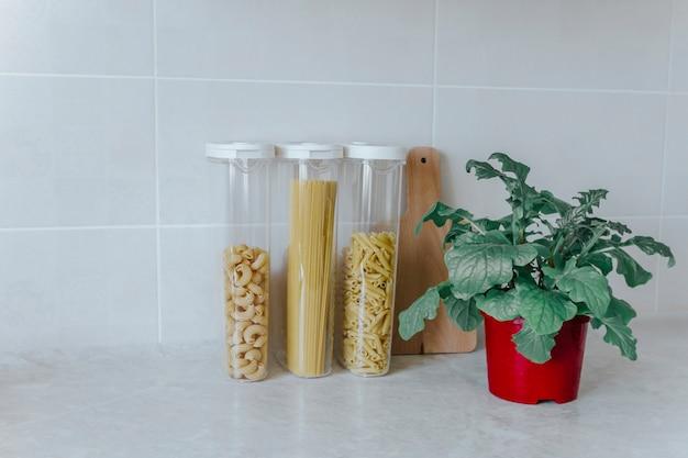 Różnorodne makarony w pojemnikach-puszkach, które stoją na kuchennym stole, obok zielonego kwiatka w czerwonym garnku i desce do krojenia