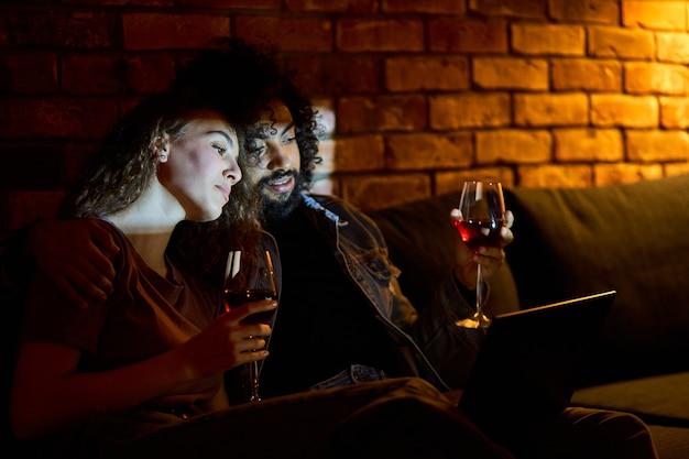 Różnorodne małżeństwo pijące czerwone wino podczas oglądania filmów, filmów, komedii. piękna kobieta uwielbia spędzać czas z chłopakiem w domu