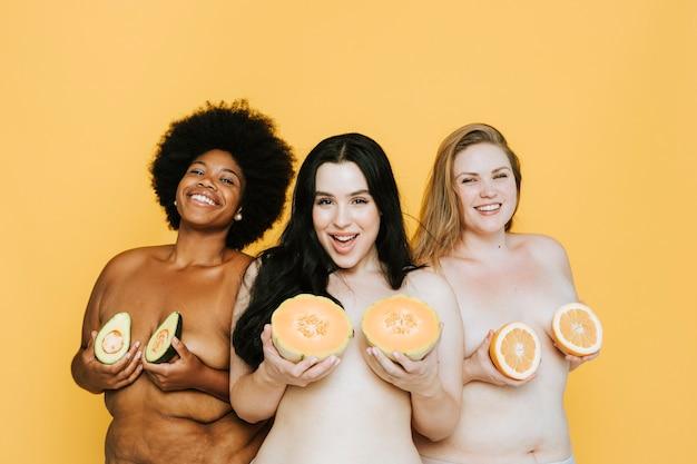Różnorodne nagie kobiety trzymające owoce na piersiach