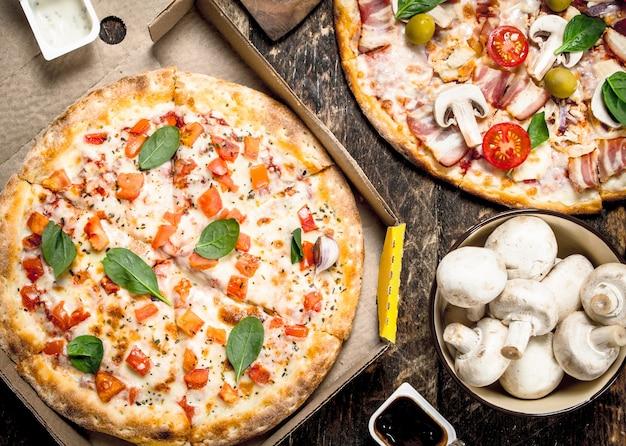 Różnorodne pizze z pieczarkami i sosem. na drewnianym tle
