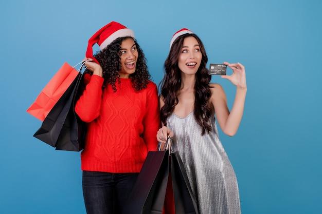 Różnorodne podekscytowane kobiety z kolorowymi torbami na zakupy i kartą kredytową odizolowywającymi nad błękitem