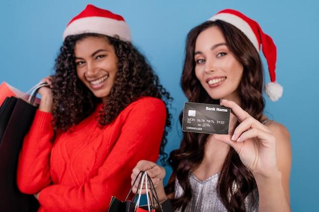 Różnorodne podekscytowane kobiety z kolorowymi torbami na zakupy i kartą kredytową