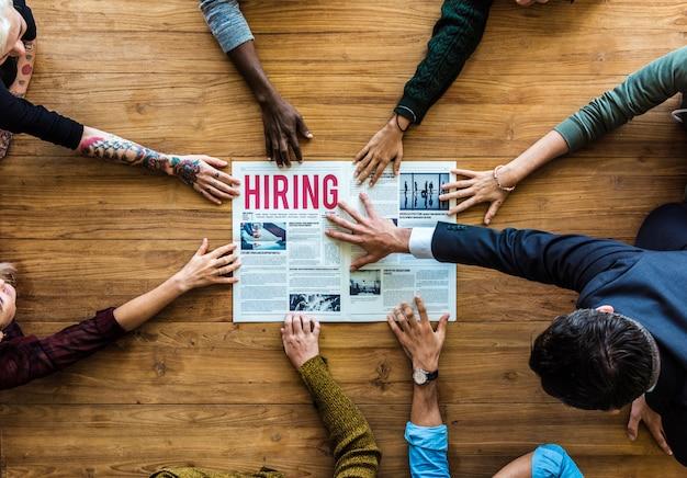 Różnorodne ręce ludzi sięgają po ogłoszenie o zatrudnieniu w gazecie
