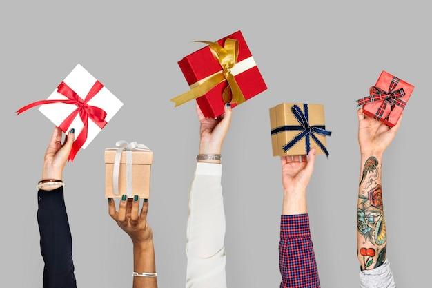 Różnorodne ręce trzymające pudełka na prezenty
