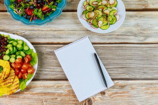 Różnorodne sałatki z notatnikiem i piórem na drewnianym stole