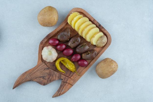 Różnorodne sfermentowane warzywa na desce, na marmurze.