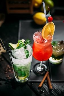 Różnorodne słodkie koktajle alkoholowe w różnych szklankach, mojito, mai tai i seks na plaży, widok z boku, w pionie
