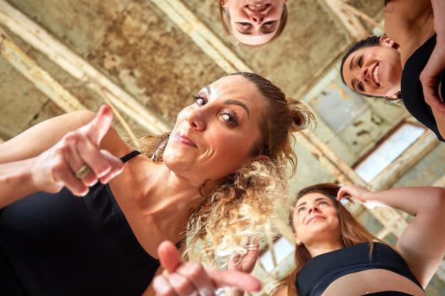 Różnorodne śmieszne dziewczyny wpólnie w okręgu na gumowych matach jest ubranym sportswear uśmiechniętego przedstawienia joga powitania gest, patrzejący kamerę, wierzchołek nad widok. namaste, symbol witania i waleczności
