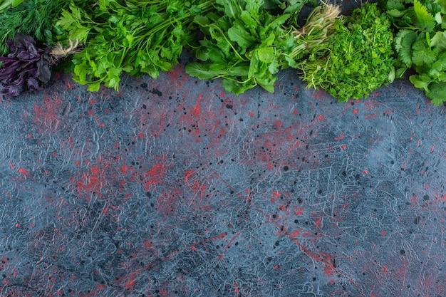 Różnorodne świeże zielenie na marmurowym tle.