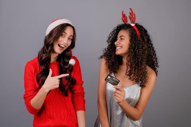 Różnorodne szczęśliwe kobiety jest ubranym santa kapelusz odizolowywającego nad popielatym z szablon kredytową kartą