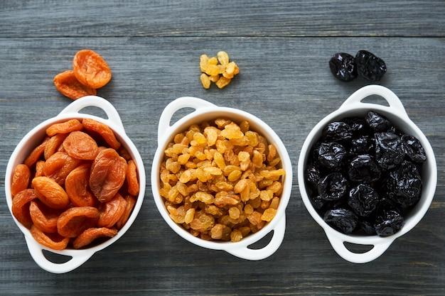 Różnorodne wysuszone owoc w białych pucharach na drewnianym stole