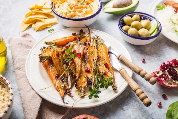 Różnorodne zdrowe wegańskie przekąski, wyśmienite dipy. hummus, pieczona marchewka, ryż z tempeh w ceramicznych misach oglądanych z góry, żywność na bazie roślin