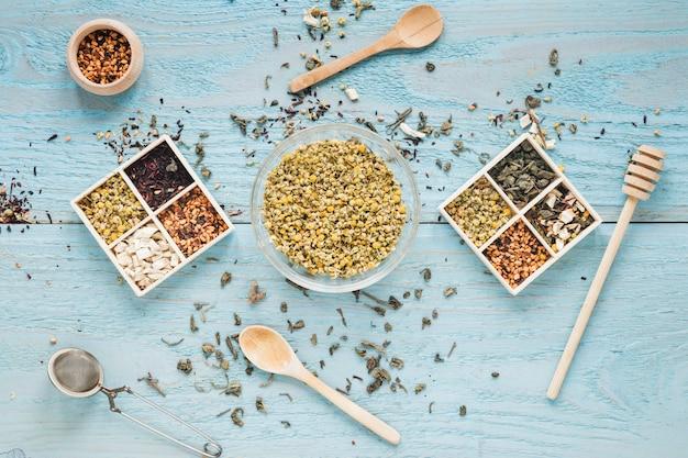 Różnorodne zioła; łyżka; miód; sitko do herbaty i suszone chińskie kwiaty chryzantemy układają się na stole