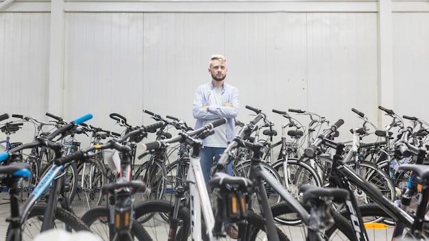 Różnorodni bicykle otacza męską mechanik pozycję w warsztacie