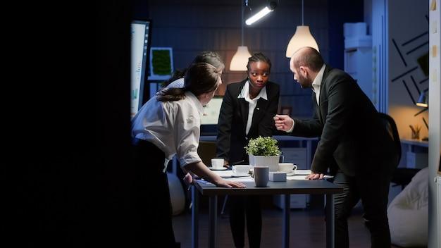 Różnorodni biznesmeni omawiają papierkową robotę kierowniczą stojąc przy stole konferencyjnym