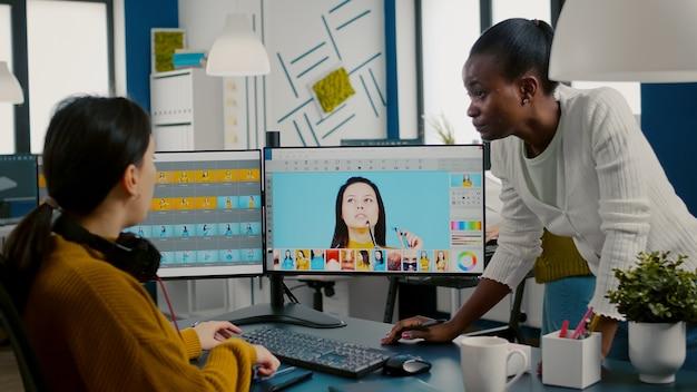 Różnorodni edytorzy zdjęć siedzą w kreatywnym miejscu pracy i retuszują zdjęcia afrykański reżyser sprawdzający kolor...