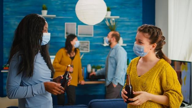 Różnorodni etniczni przyjaciele spędzają razem czas w mieszkaniu, rozmawiając w salonie, zachowując dystans społeczny, nosząc maskę na twarz, jako profilaktykę rozprzestrzeniania się koronawirusa w trakcie globalnej pandemii.