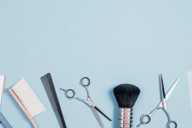 Różnorodni fryzjer męski narzędzia układali z rzędu na błękitnym tle