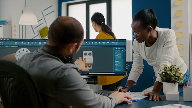 Różnorodni inżynierowie pracujący na komputerze przy projektowaniu elementów mechanicznych
