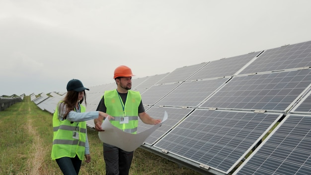 Różnorodni inżynierowie rozmawiają i sprawdzają plan programu stojąc przy farmie energii słonecznej. kobieta i mężczyzna w odzieży roboczej i twardym kasku omawiając projekt. koncepcja zielonej energii. pole paneli słonecznych.