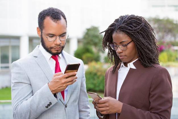 Różnorodni koledzy biznesowi korzystający ze smartfonów