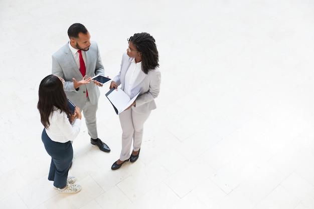 Różnorodni koledzy biznesowi omawiający problemy związane z pracą