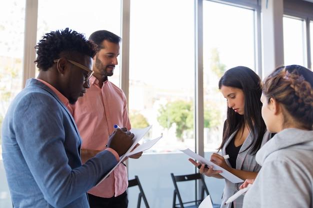 Różnorodni koledzy robią notatki, dzieląc się pomysłami