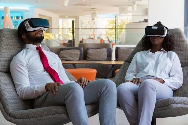 Różnorodni koledzy w okularach vr relaksujący w salonie biurowym