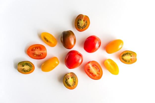 Różnorodni kolorowi pomidory odizolowywający na biel ścianie. widok z góry, leżał płasko. kreatywny układ