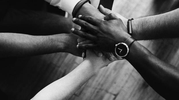 Różnorodni ludzie podają sobie ręce na środku