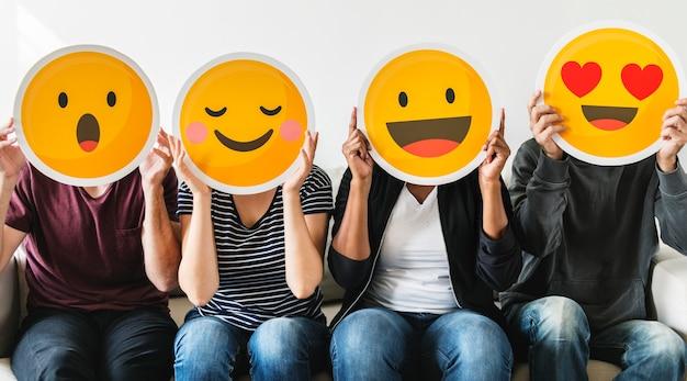Różnorodni ludzie trzyma emoticon