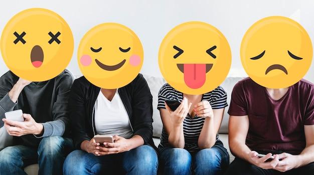 Różnorodni ludzie z emotikonami korzystającymi z telefonów komórkowych