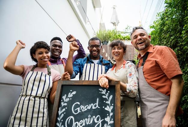 Różnorodni ludzie z wielkim otwarciem podpisują pierwszy dzień biznesu