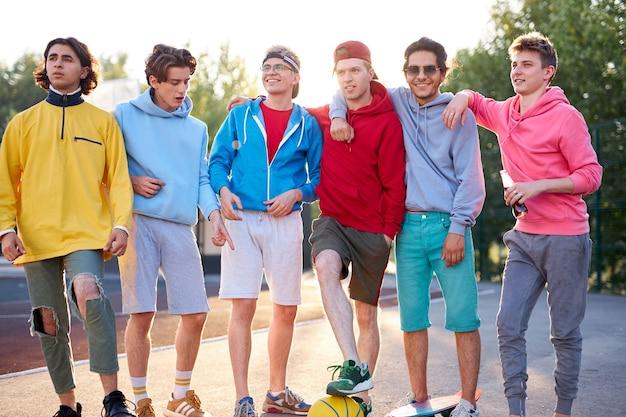 Różnorodni młodzi chłopcy z miasta są gotowi do wspólnej gry w koszykówkę