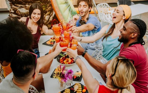 Różnorodni młodzi ludzie bawią się, świętując koktajle